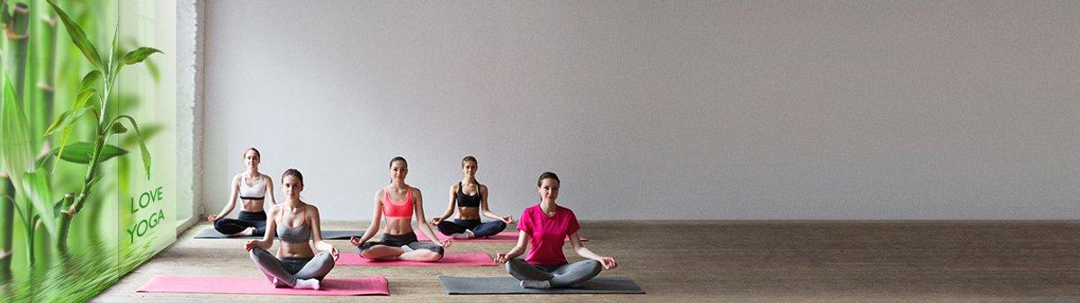 Raum wo Frauen auf dem Boden sitzen und Yoga machen. Links am Fenster Schiebegardinen mit einem Bambusmotiv